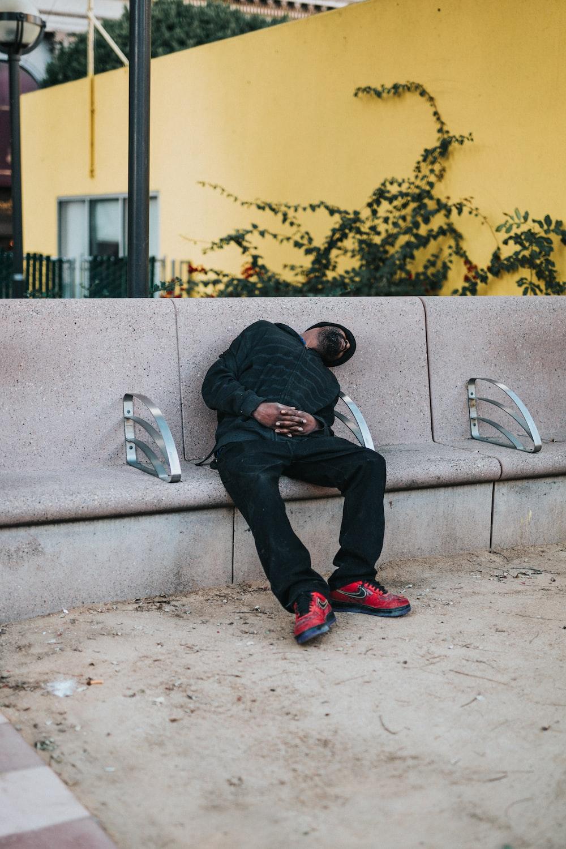 man sleeping on beige concrete bench on focus photo