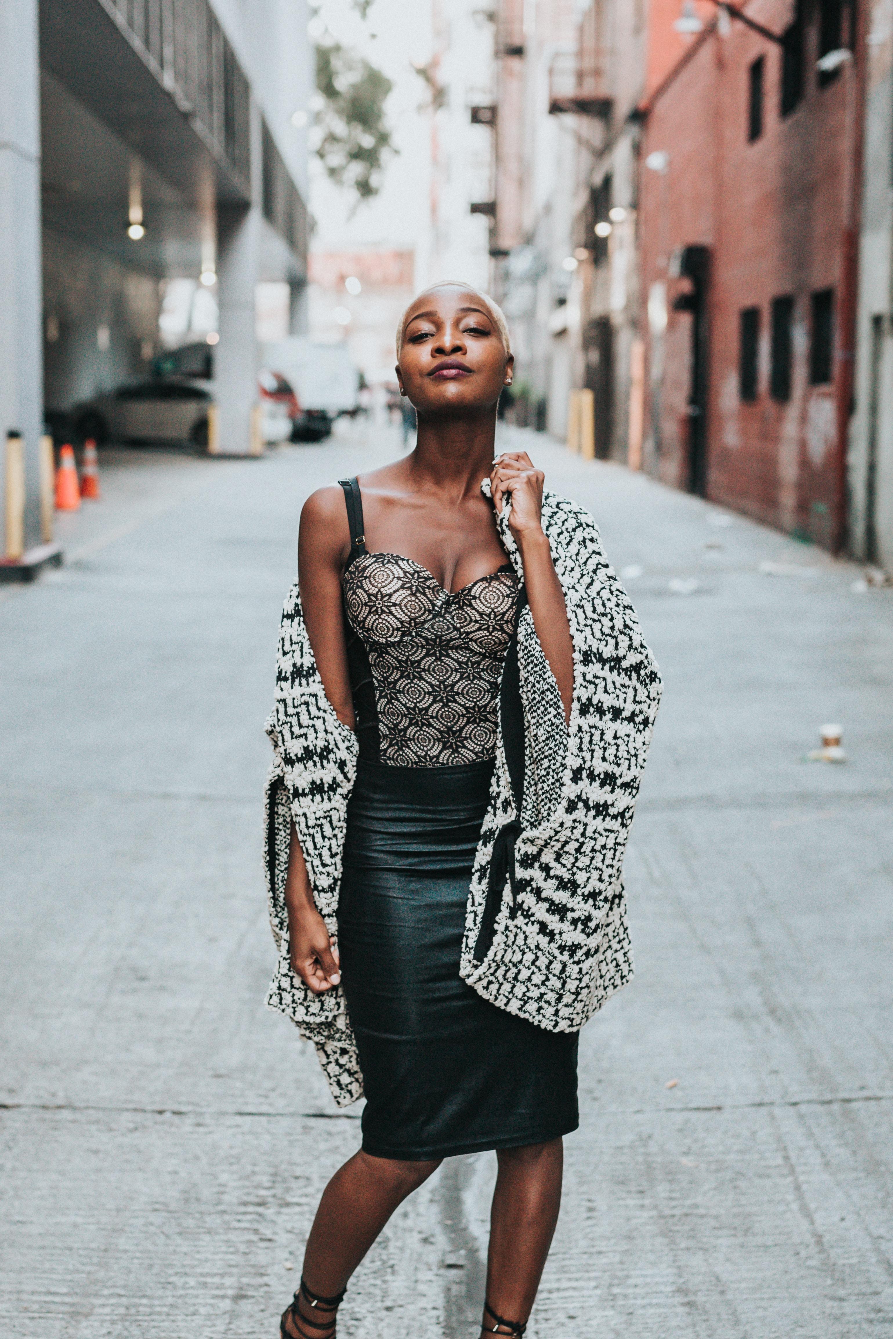 woman wearing black and gray dress standing between buildigs