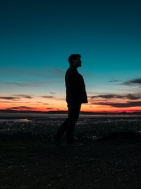 silhouette on man standing on seashore