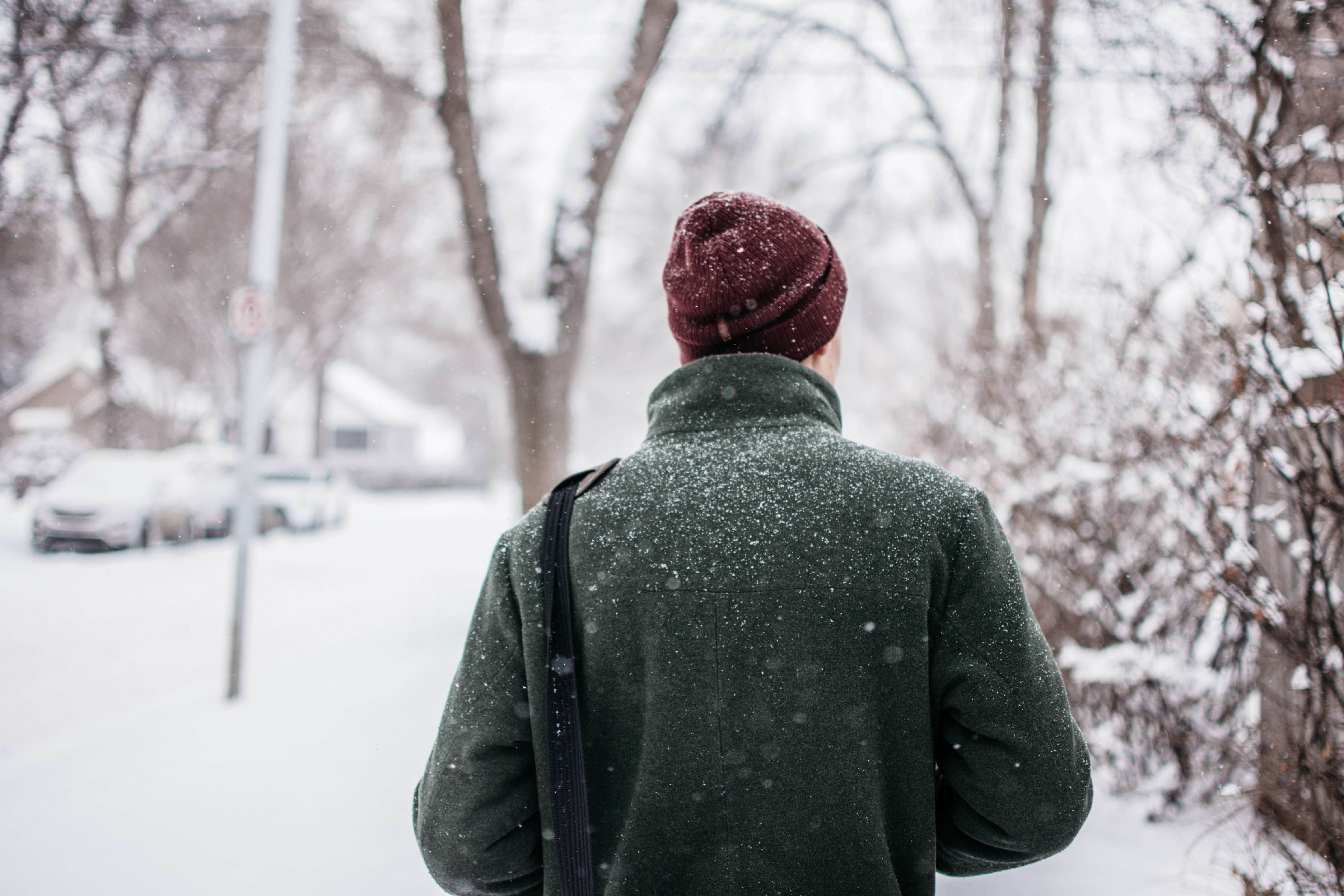 person in red knit cap and green top looking at trees with snow