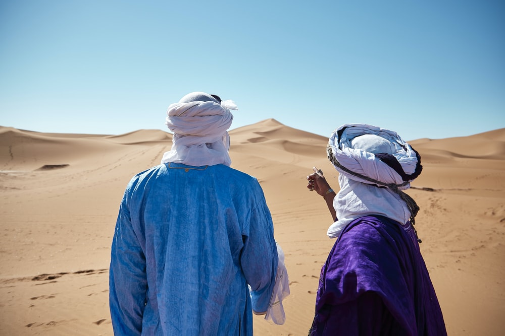 two persons standing on desert