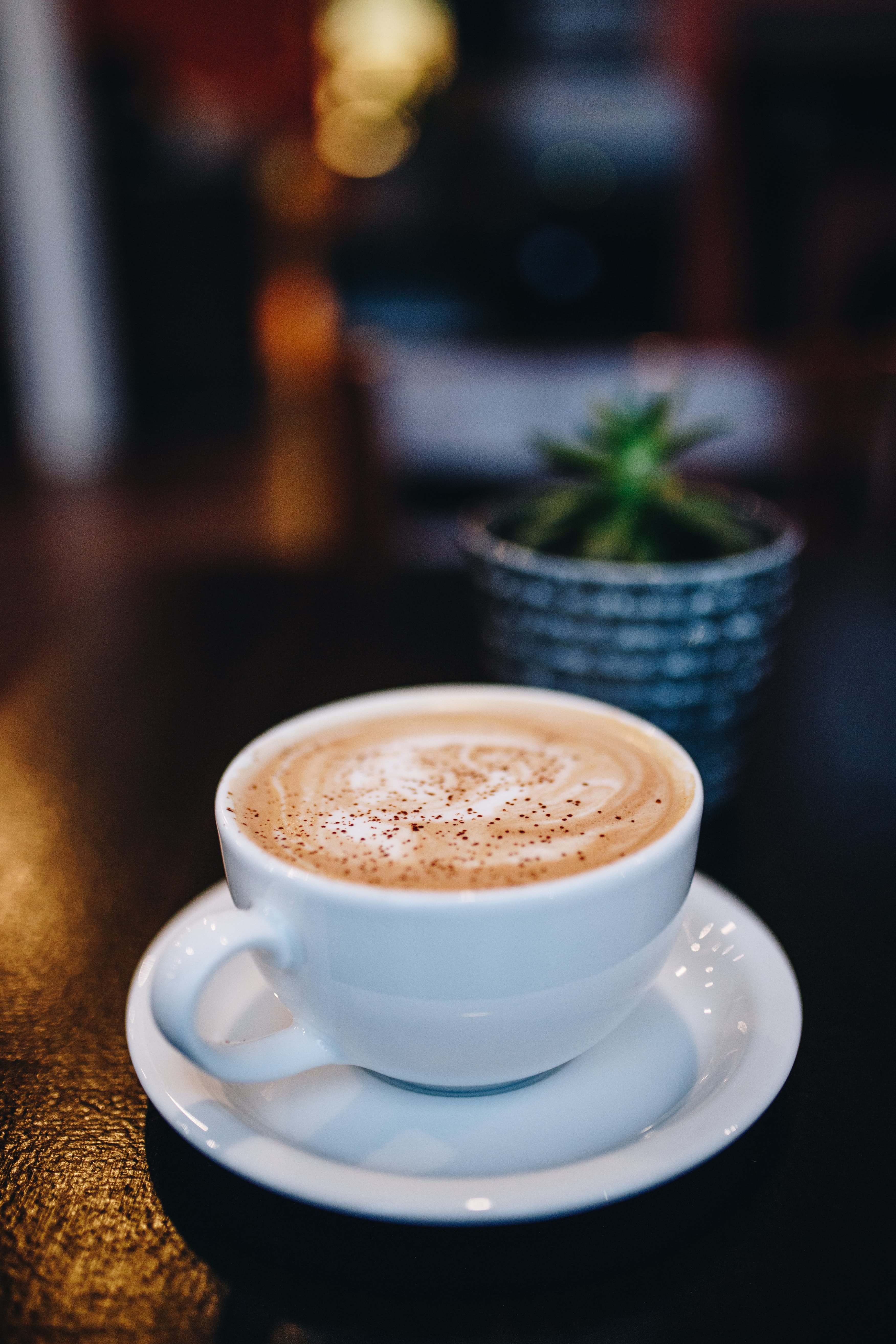 white ceramic teacup on white ceramic saucer filled with coffee in focus photography
