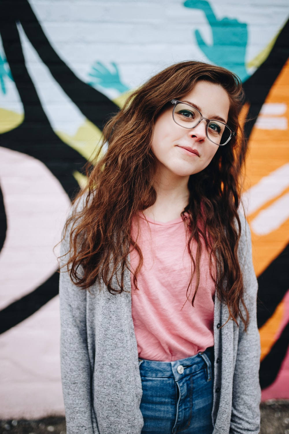 girl wearing eyeglasses with silver frames behind graffiti