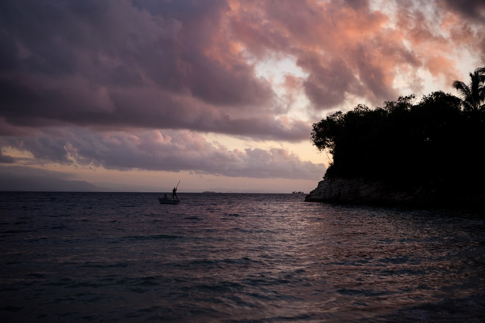 sail boat on body of water near island
