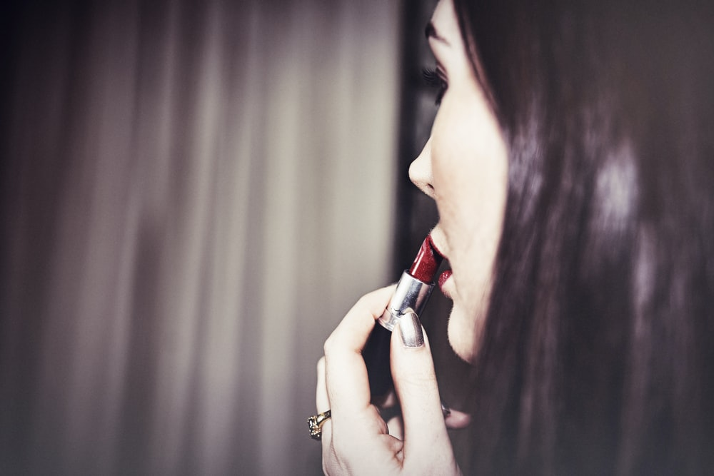 woman putting red lipstick in her lips