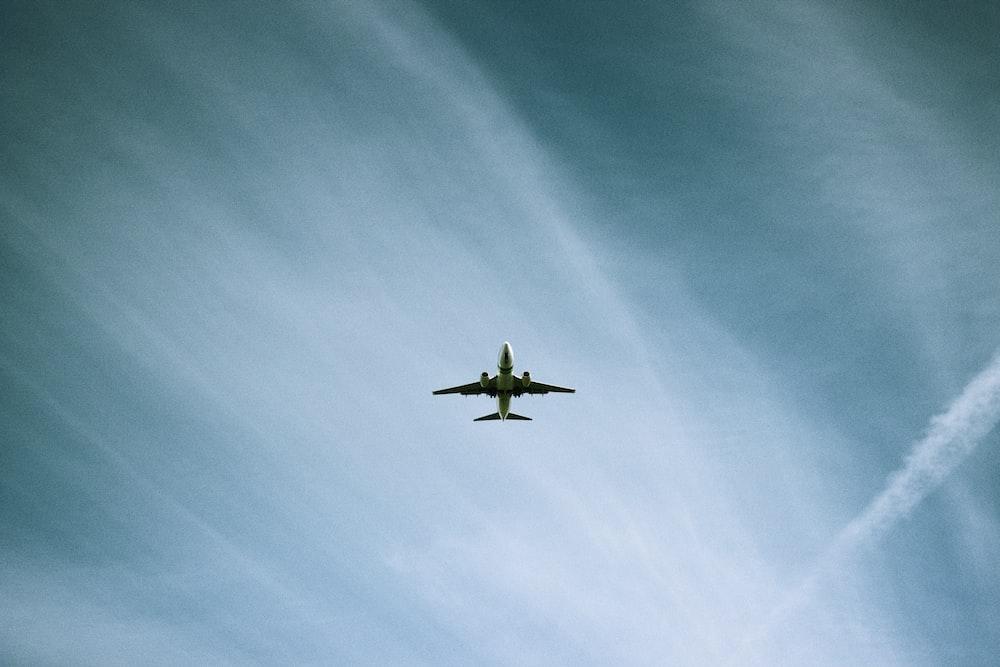 white airplane flying under blue sky