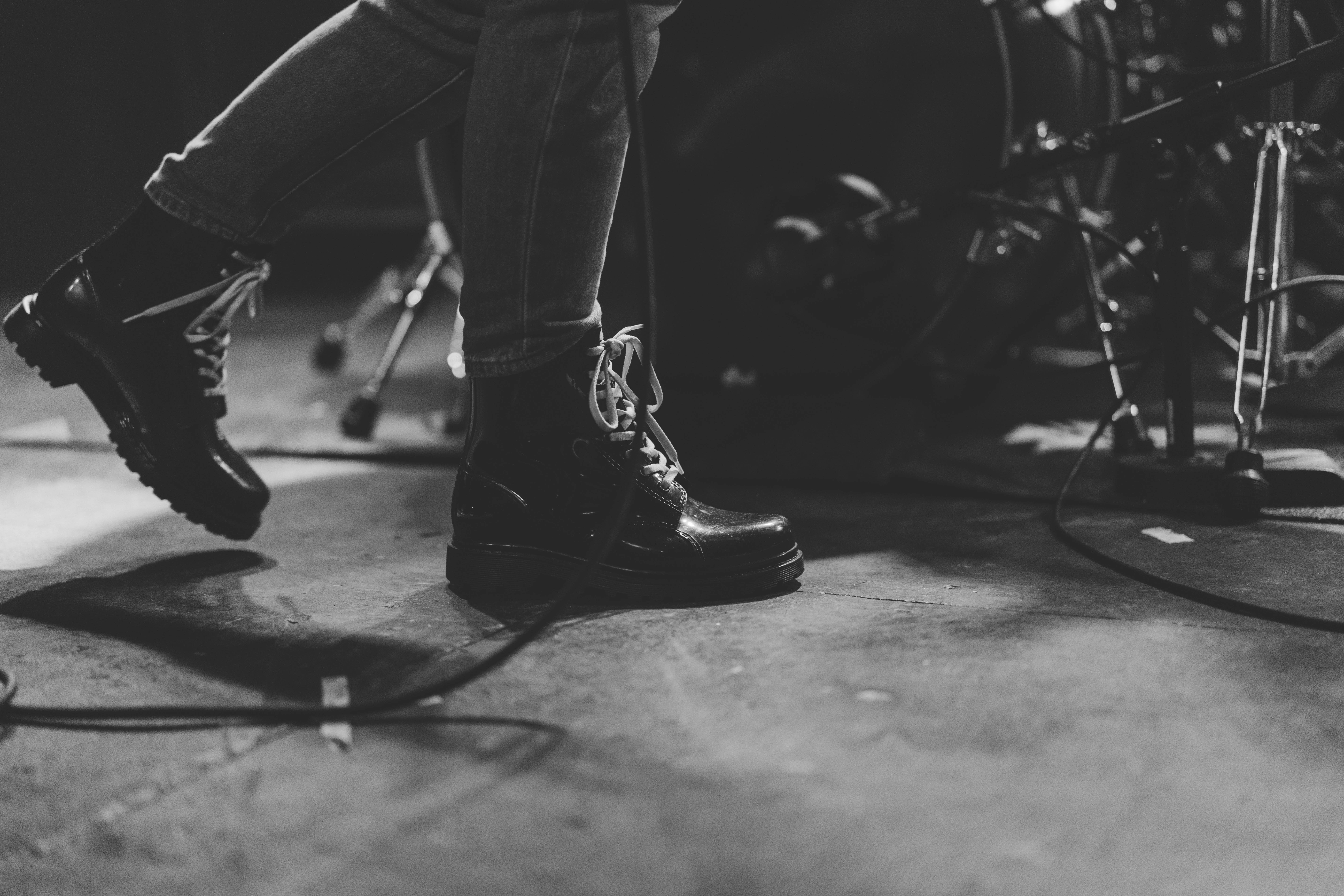 person in black leather boots walking beside of drum set
