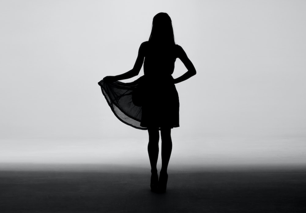 silhouette of woman holding skirt of dress