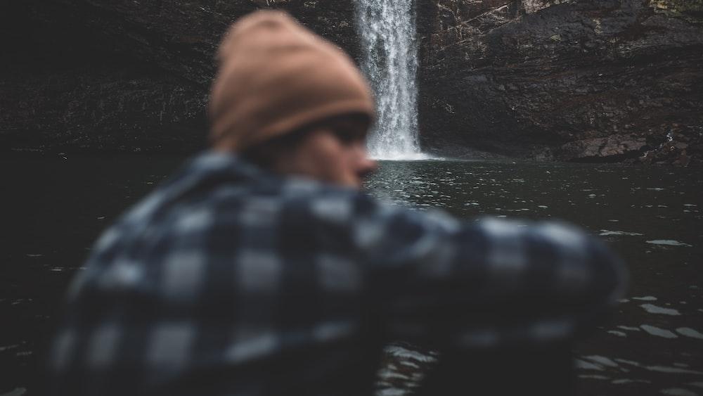 person sitting beside waterfalls