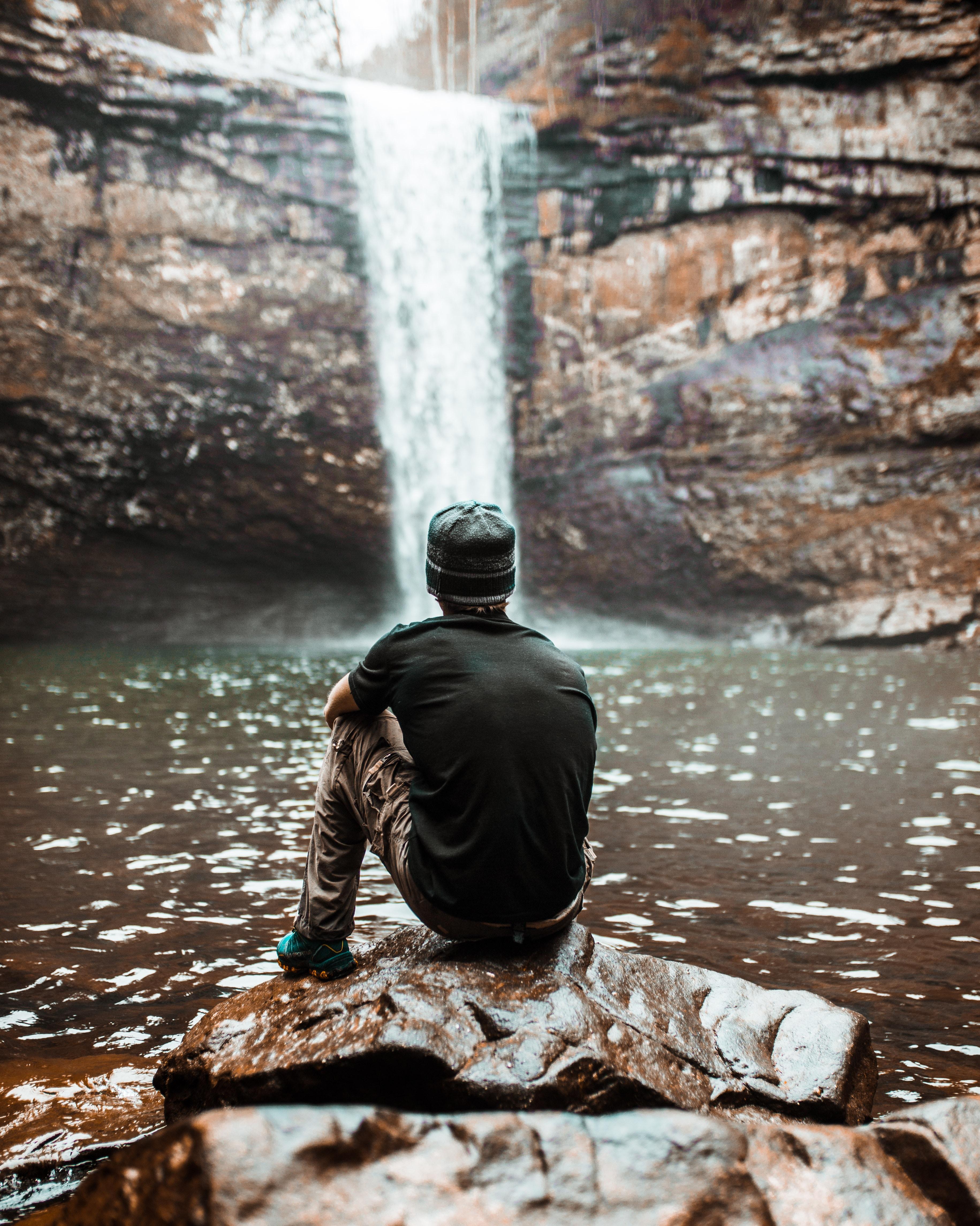 man sitting on brown rock near waterfalls at day time