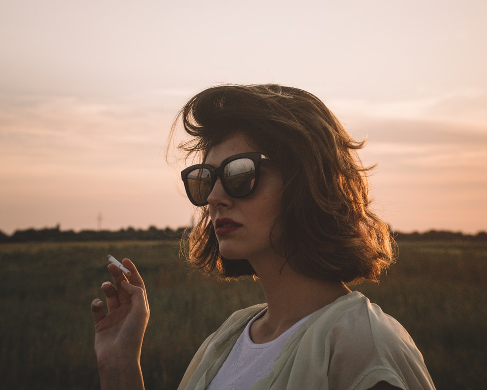 selective focus photography of woman holding cigarette