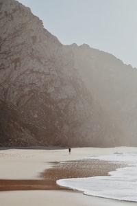 person walking seaside during daytime