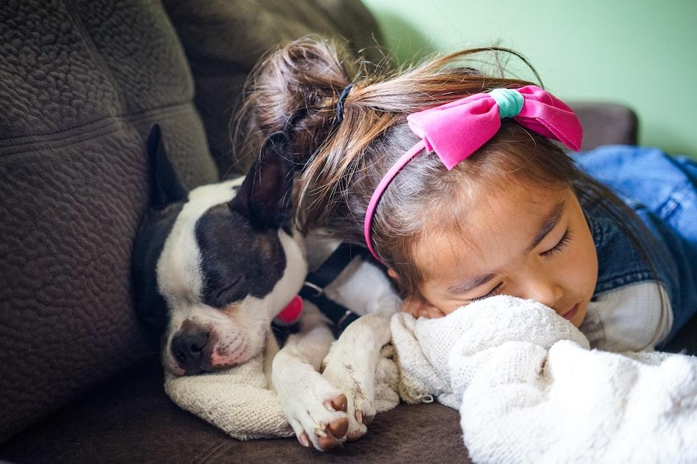 girl sleeping beside a dog on the sofa