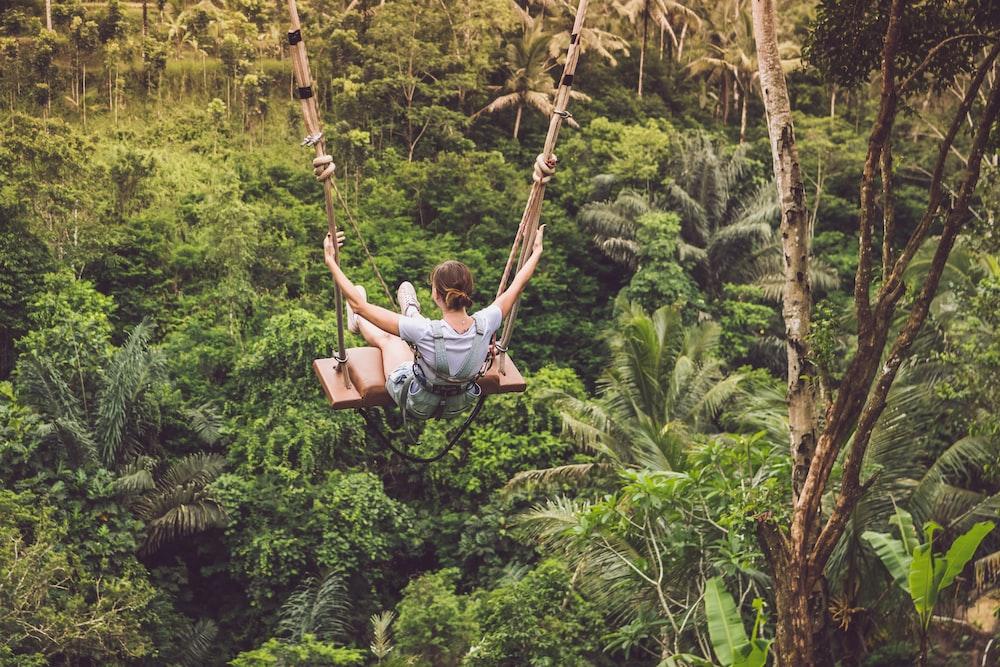 woman riding on swing hanged on tree