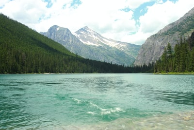 calm body of water near mountain glacier national park zoom background