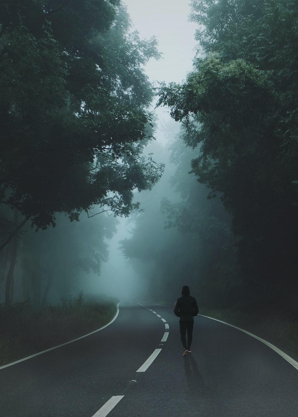 man wearing black hoodie and pants walking on gray top road
