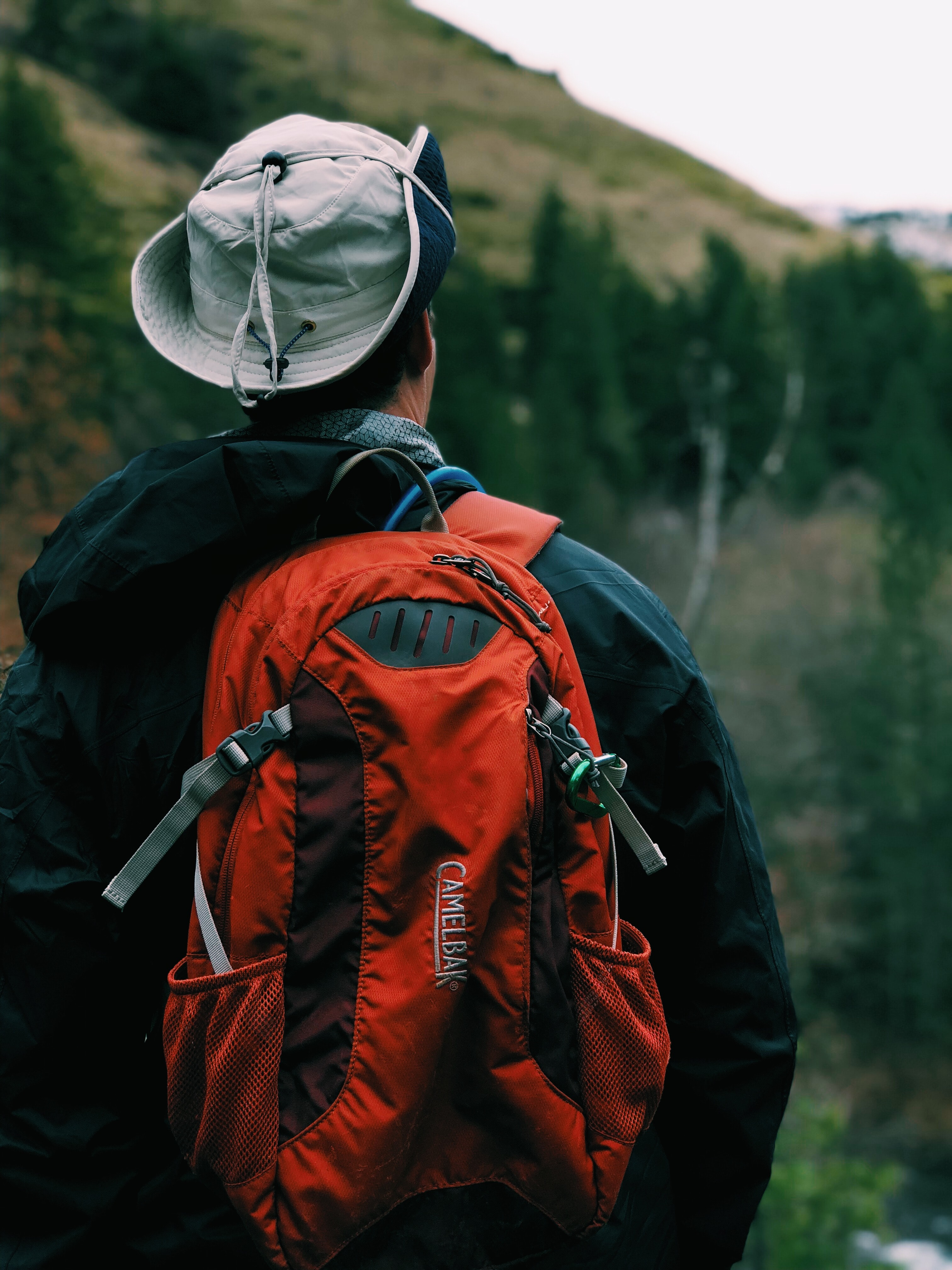 man in black coat wearing red backpack standing in front of mountain during daytime