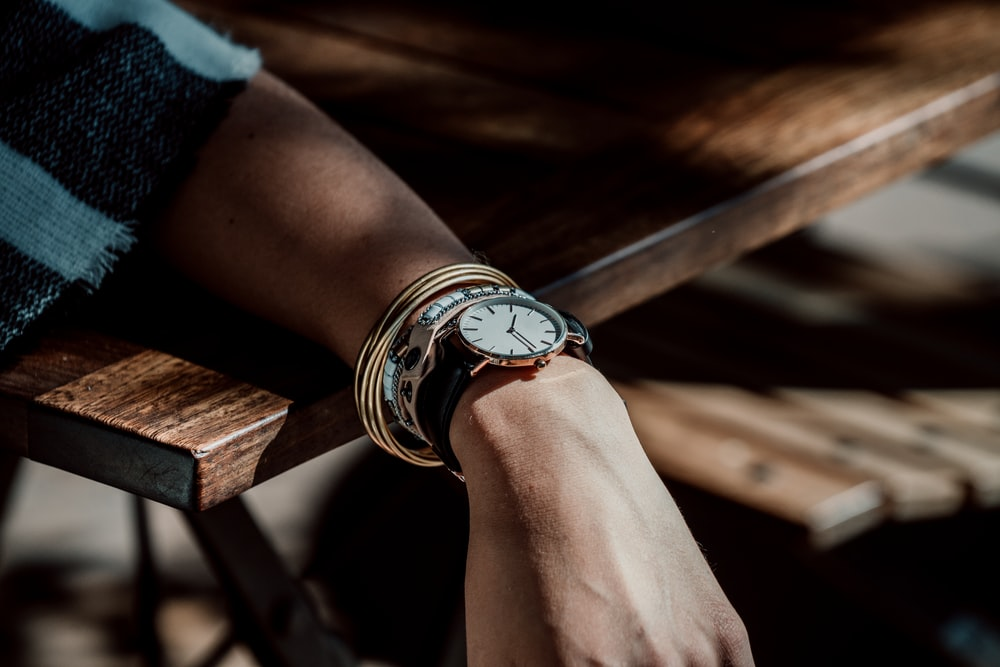 person wearing analog watch leaning on the table