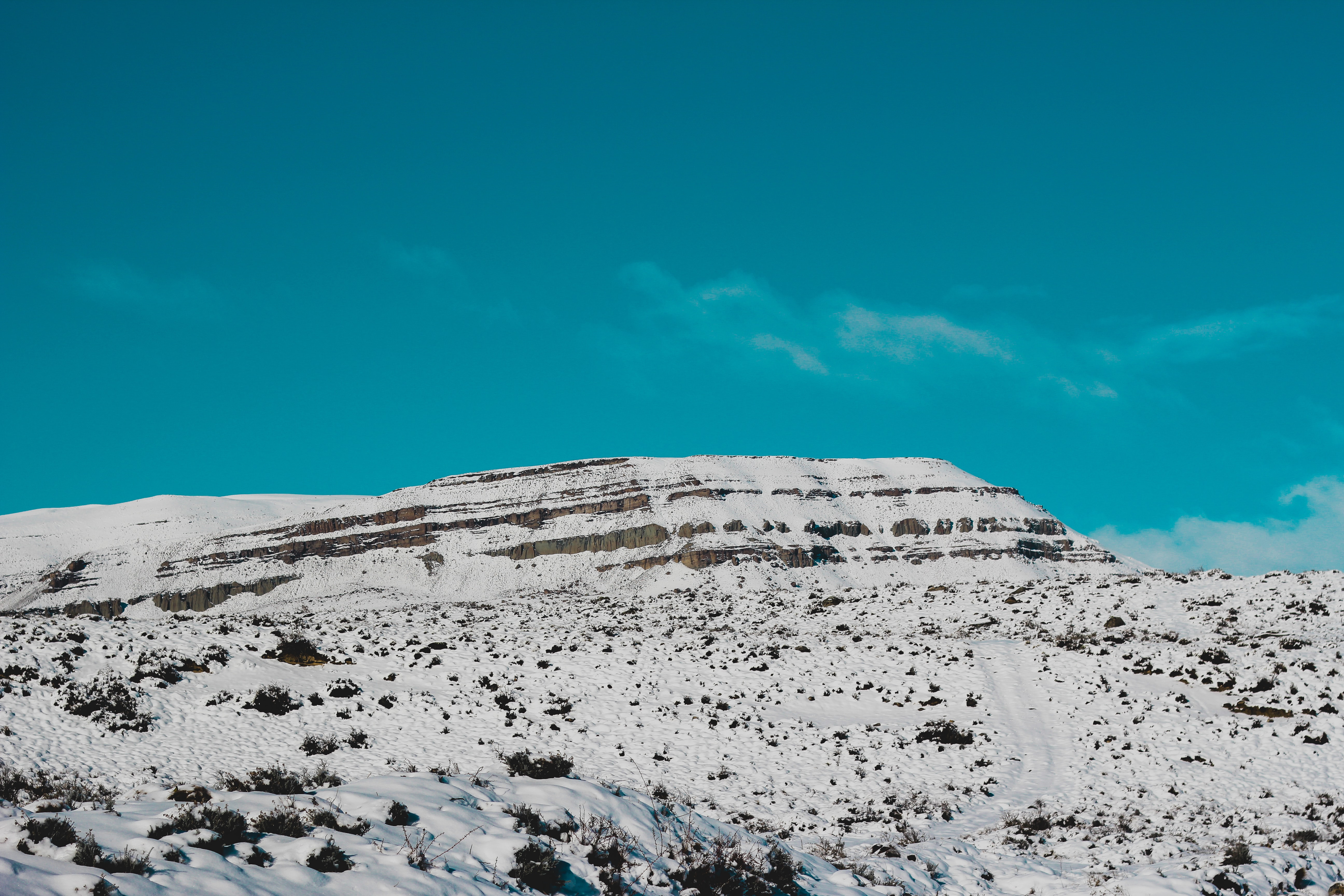 mountain covered with snow under green sky