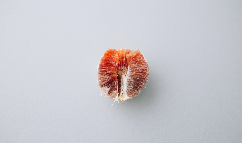 orange pomelo on gray surface