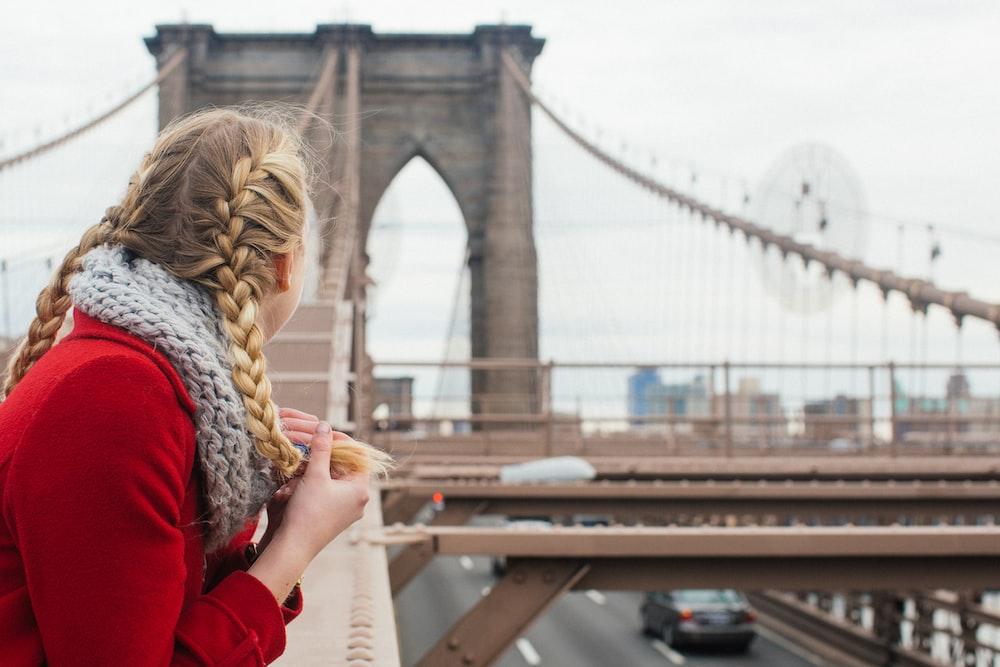 woman wearing red long-sleeved top leaning on metal beam while looking at bridge
