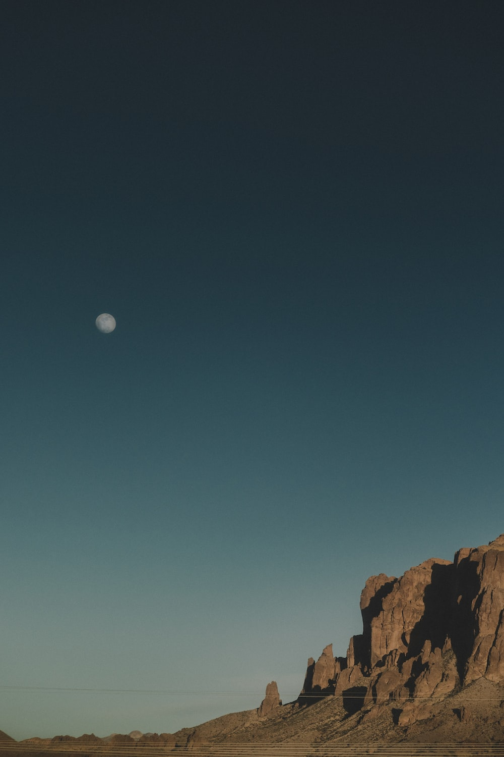 rock formation under clear skies and moon