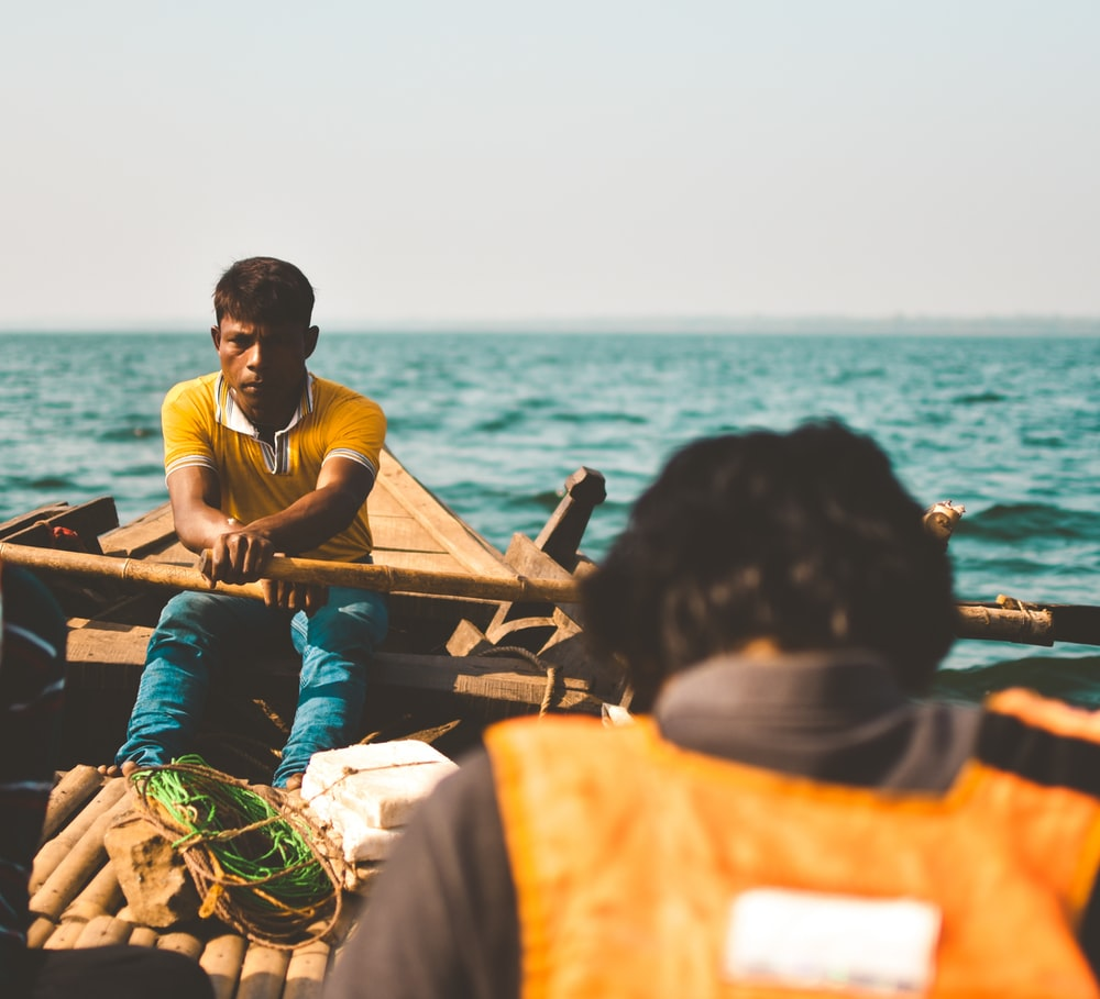 man padding inside boat on sea during daytime