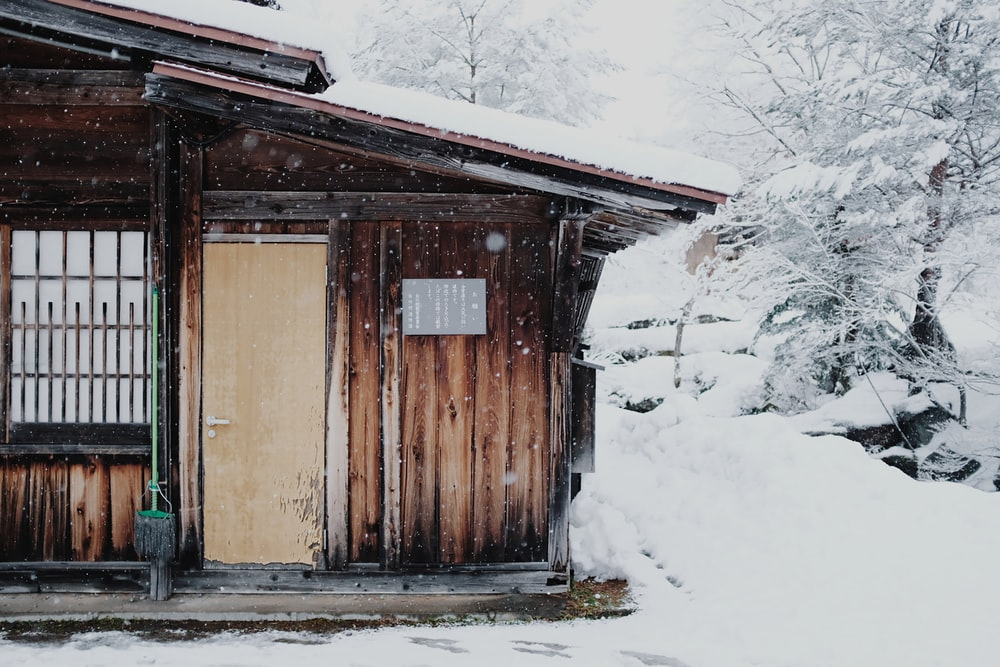 brown wooden house covered with snow at daytime