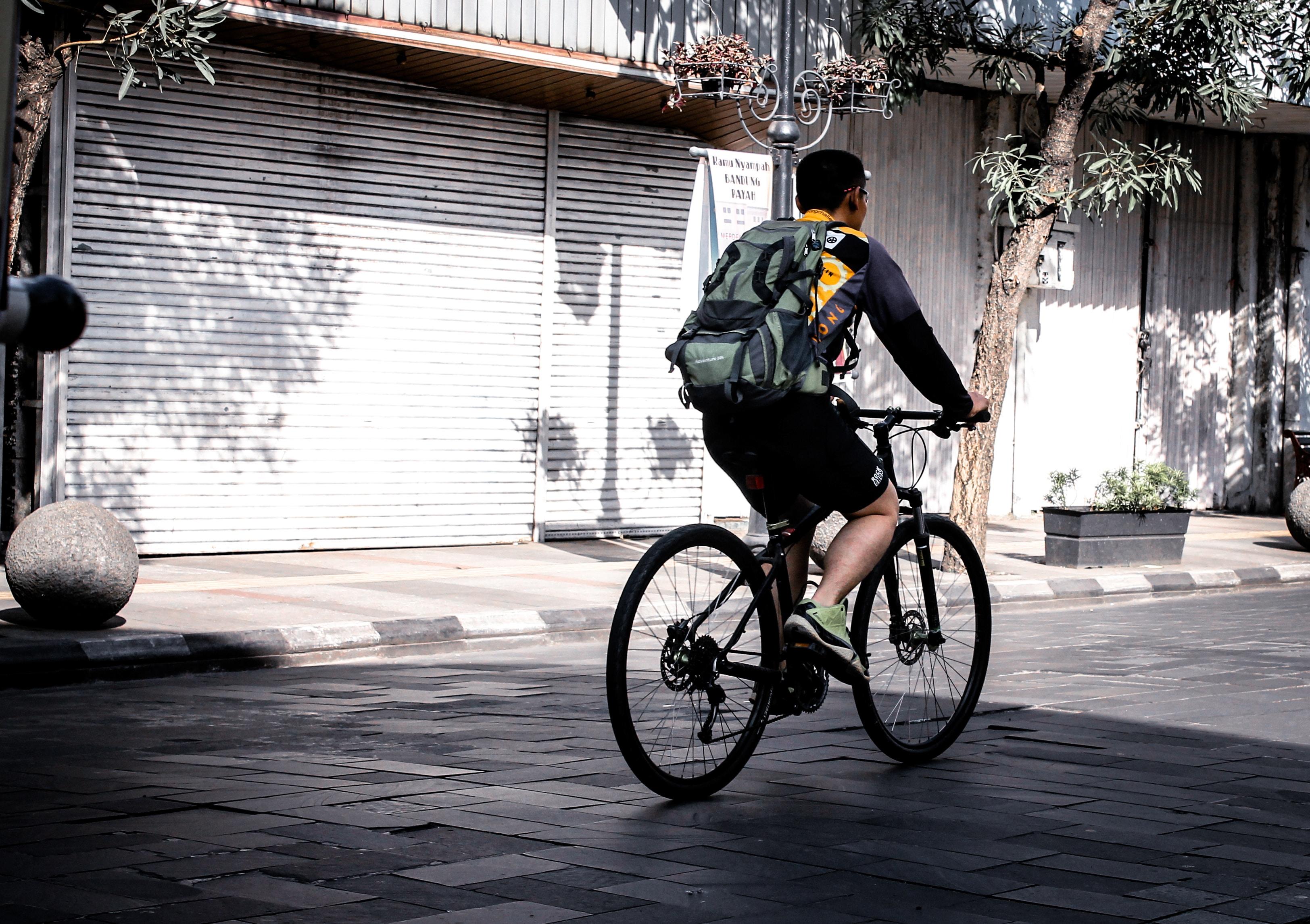 man riding bicycle near shutter roller