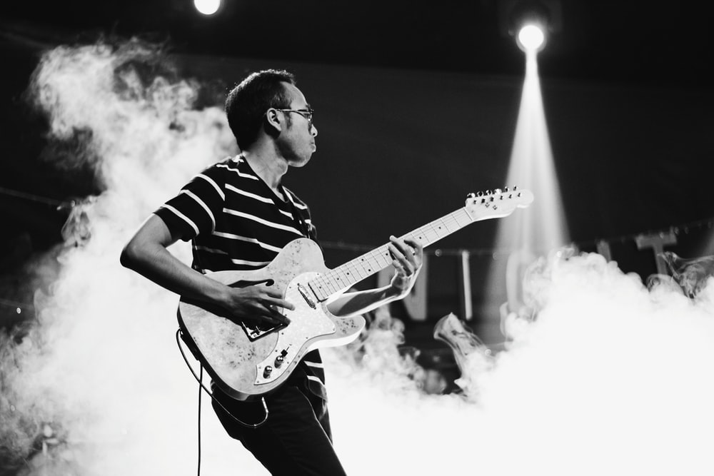 man playing guitar on stage with smoke