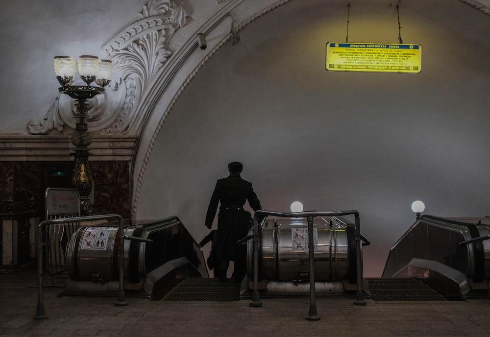 silhouette of man standing near floor lamp