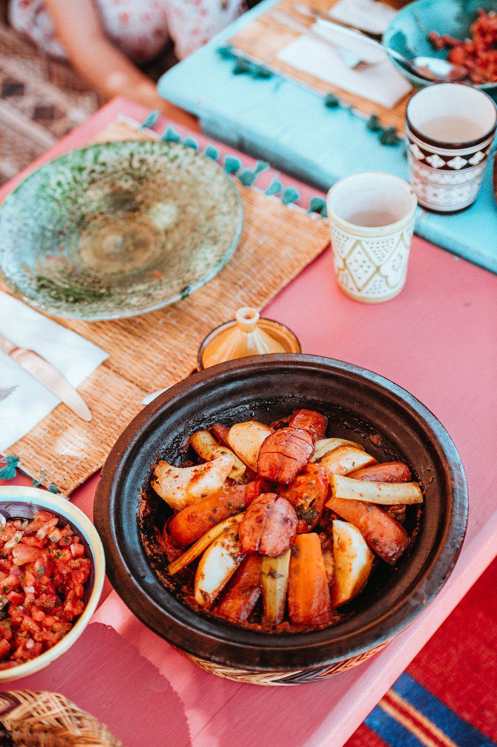 flavored food on bowl beside plate on top of table