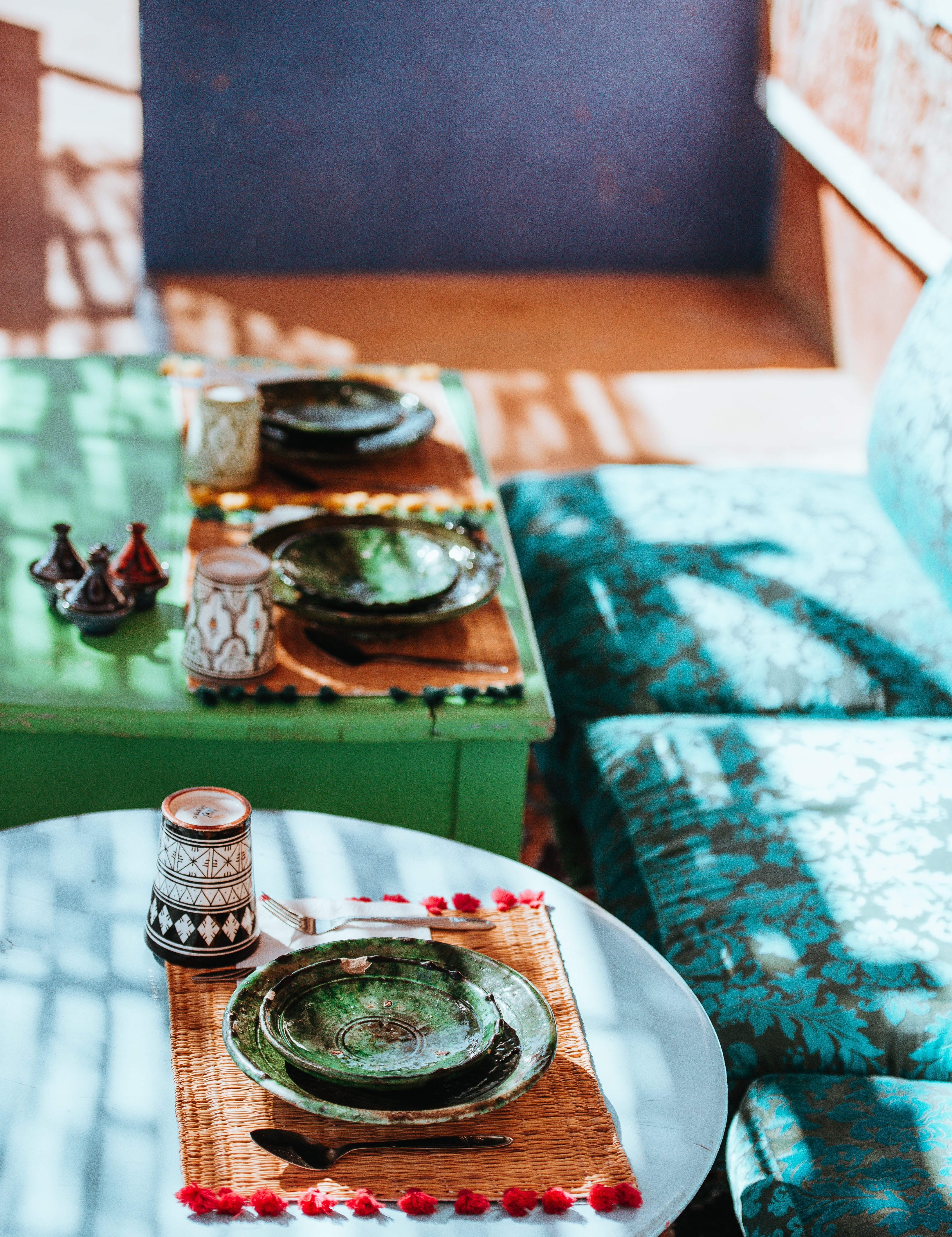 green ceramic saucers on green and teal tables