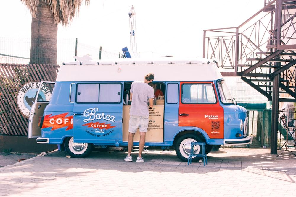 man standing near blue van during daytime photo