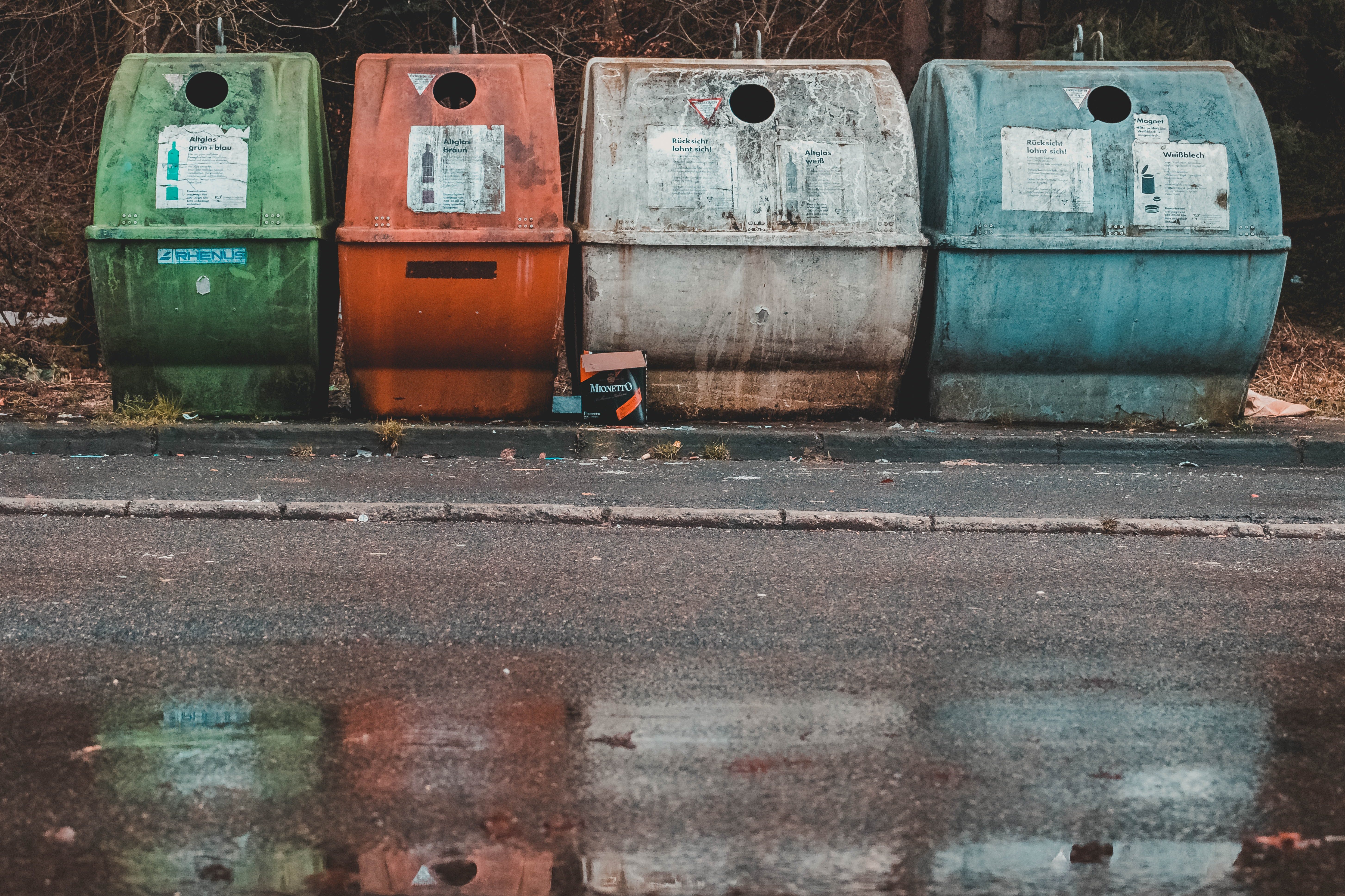 photo of four assorted-color compost pits near empty road