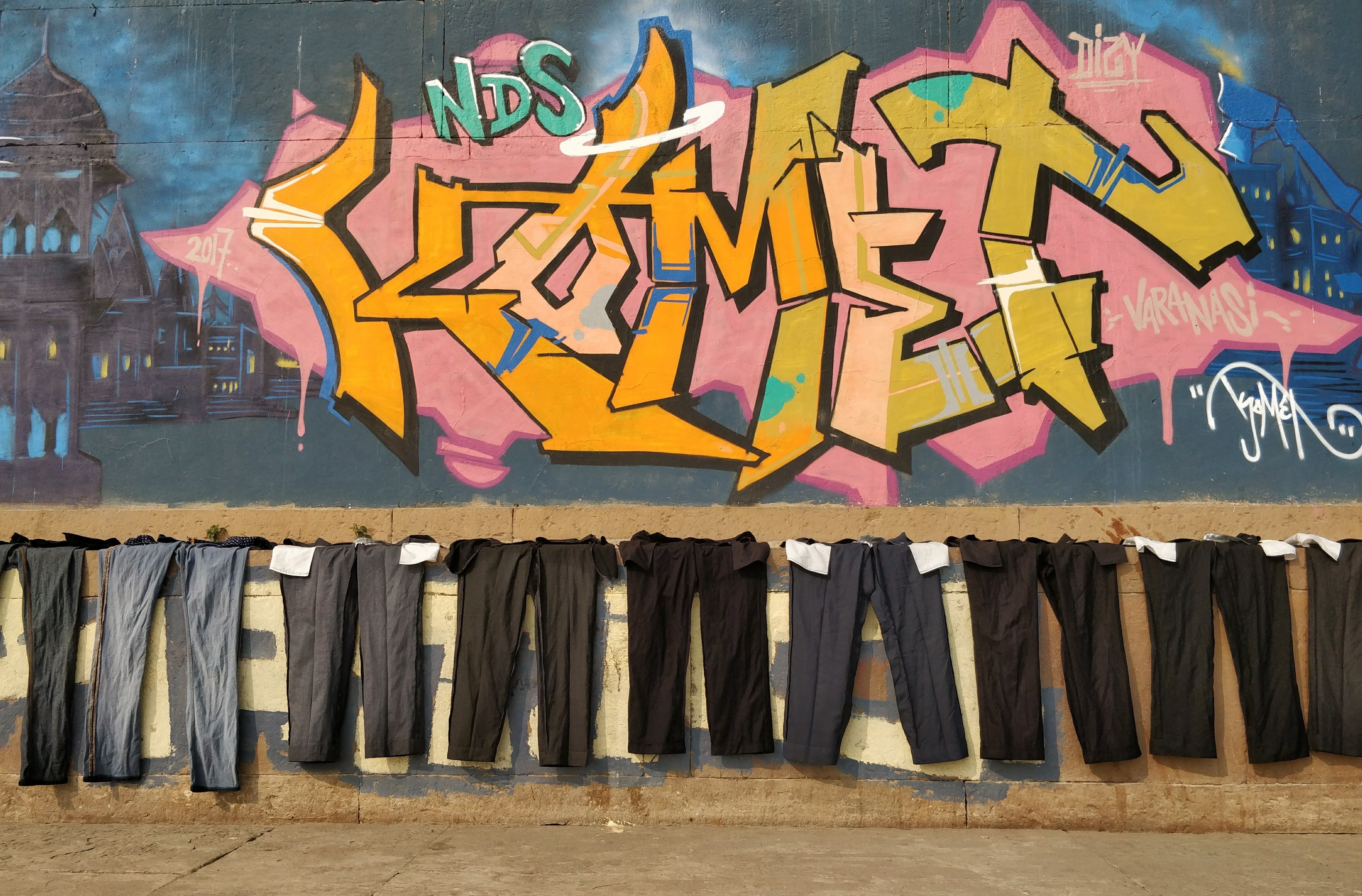 men's assorted dress pant lot in front of mural