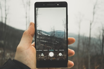 person holding black android smartphone taking picture to bare trees czechia zoom background