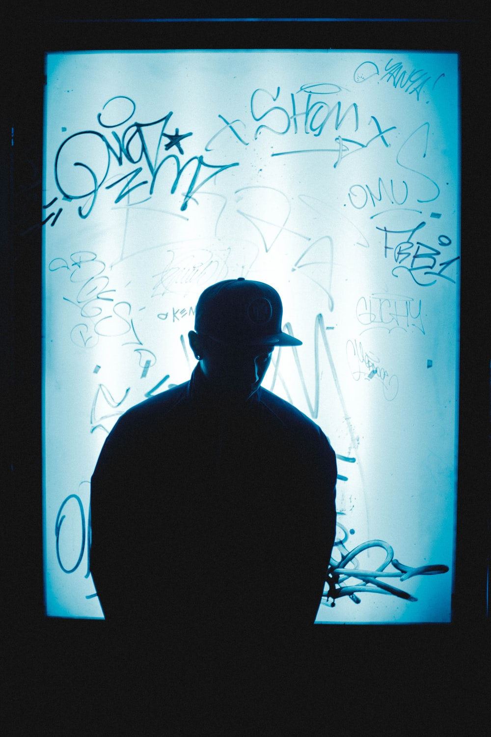 silhouette of man in front of signed poster
