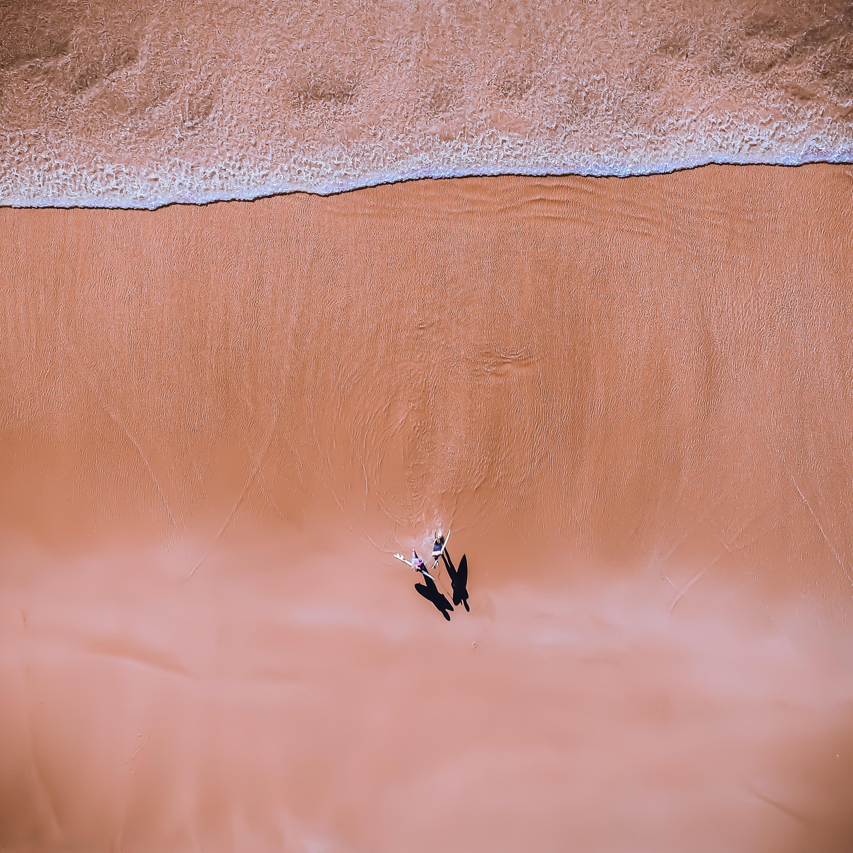 aerial photography of couple walking on seashore
