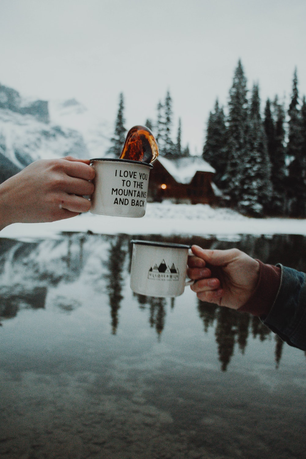 two person toasting their cups outdoors