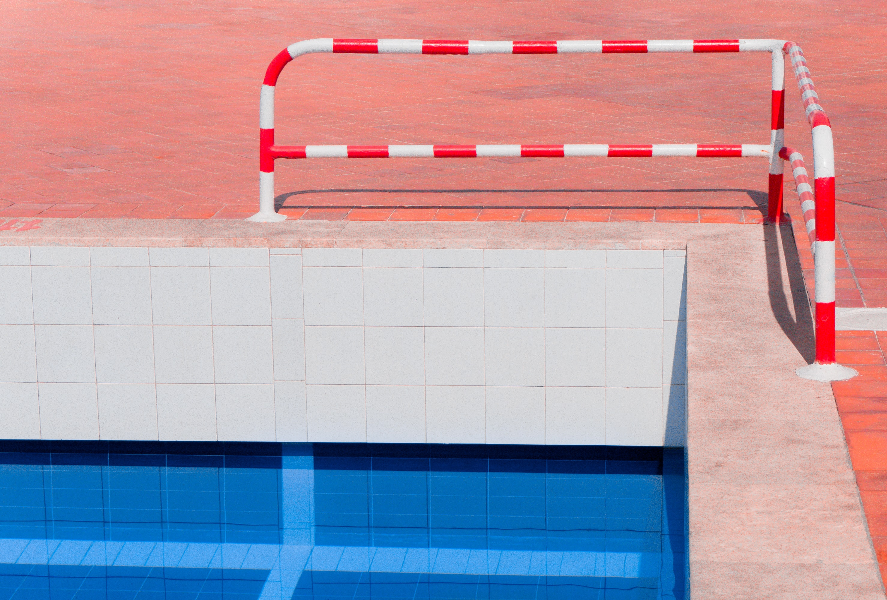 red and white stripe pool rail