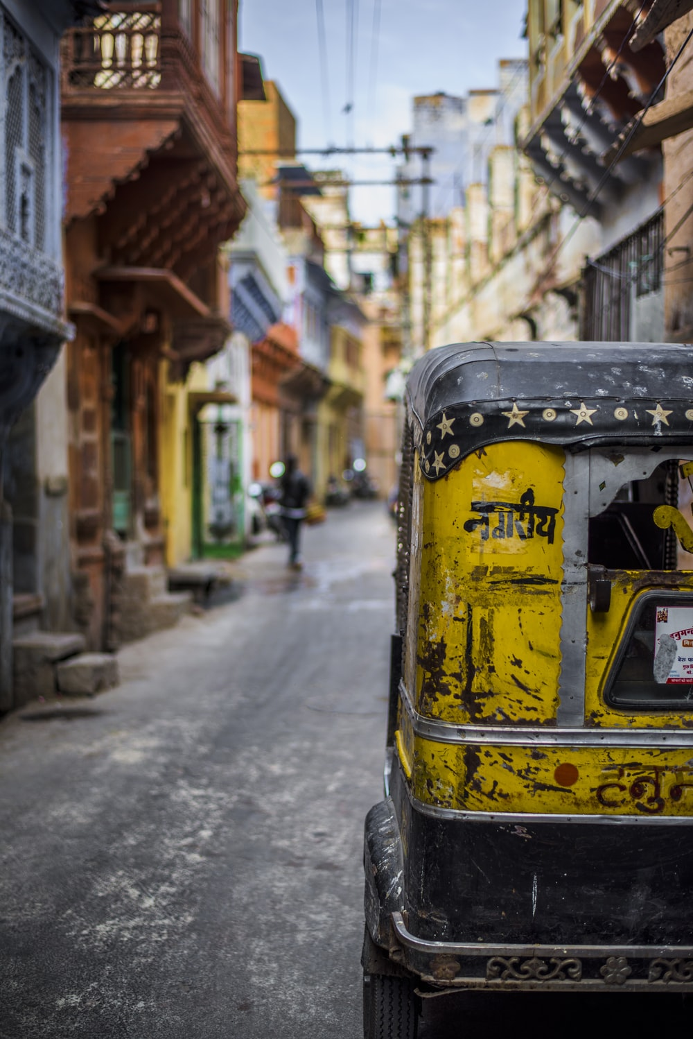 selective focus photography of yellow auto rickshaw on road