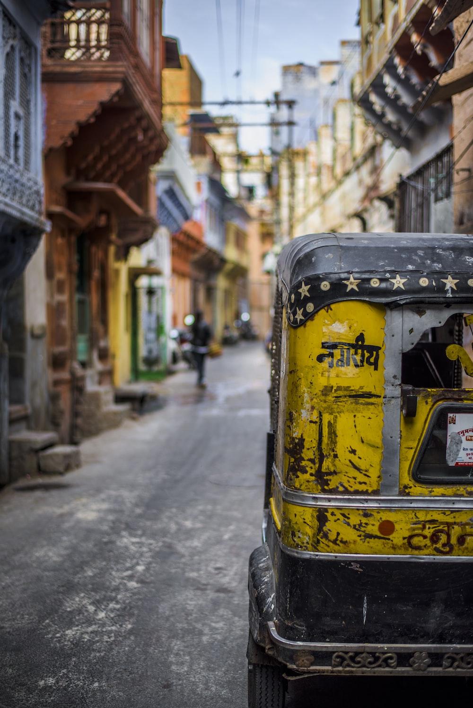 selective focus photography of yellow auto rickshaw on road