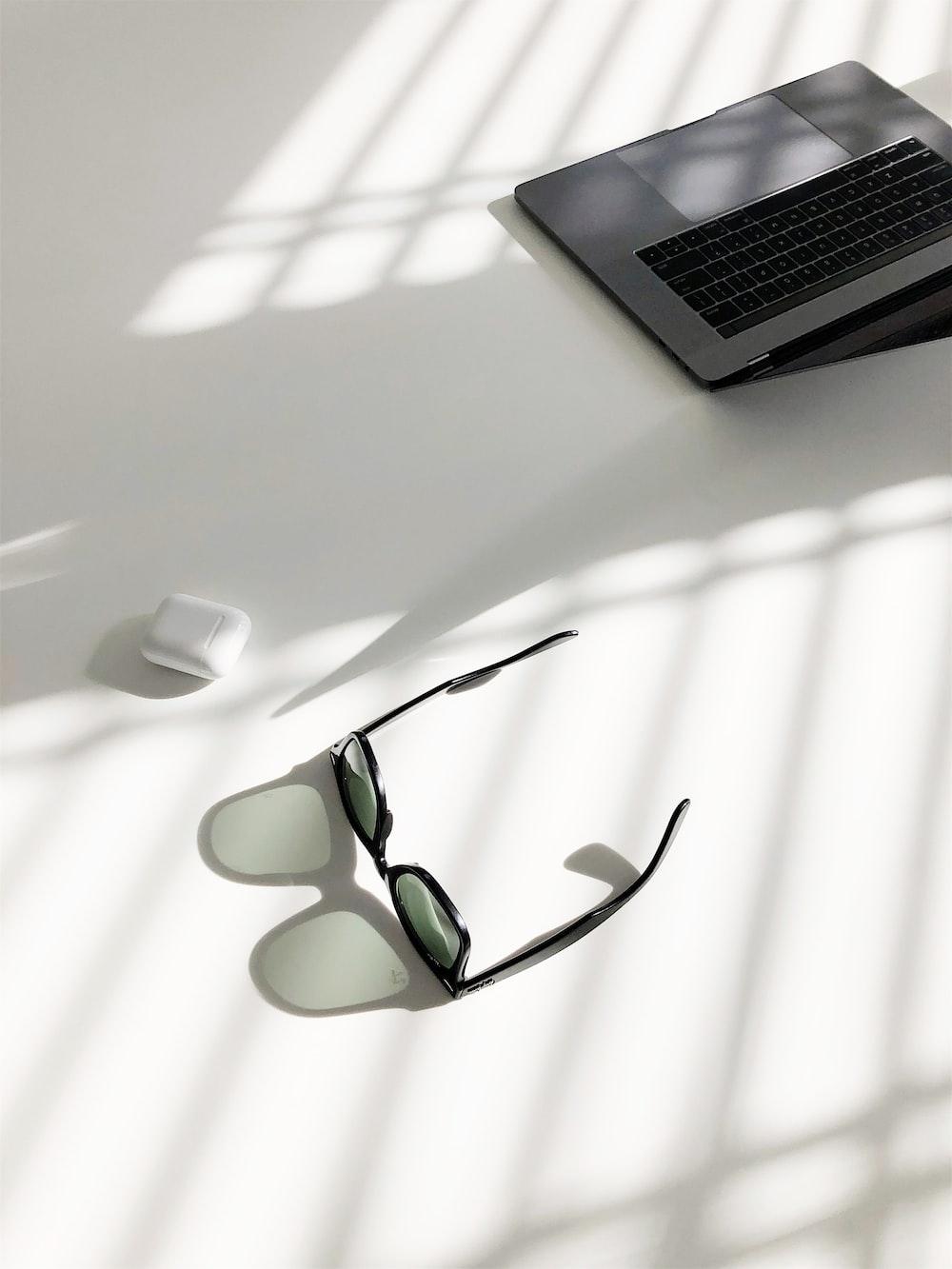 flat-lay photography of wayfarer-style sunglasses and MacBook Pro