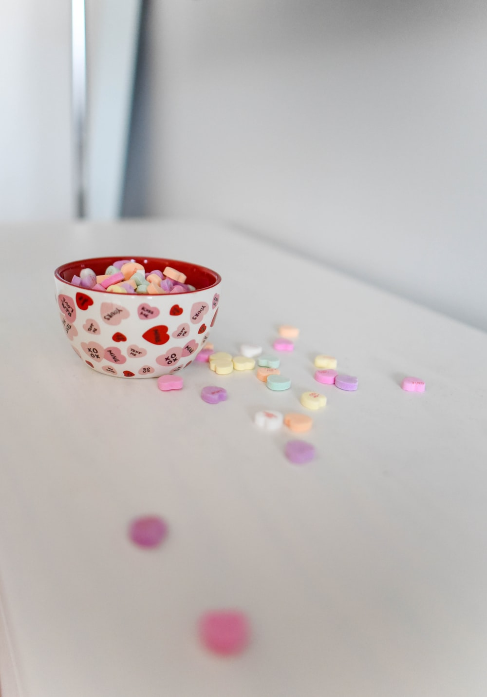 white and red ceramic bowl on white surface