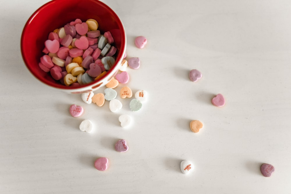 assorted-color candies and red and white ceramic bowl