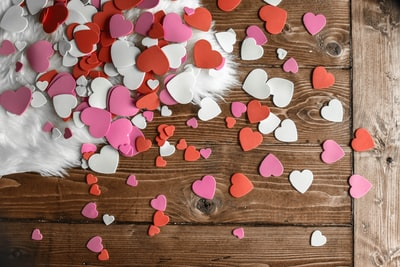 heart-shaped assorted-color cutout decors place on wooden surface valentine's day zoom background