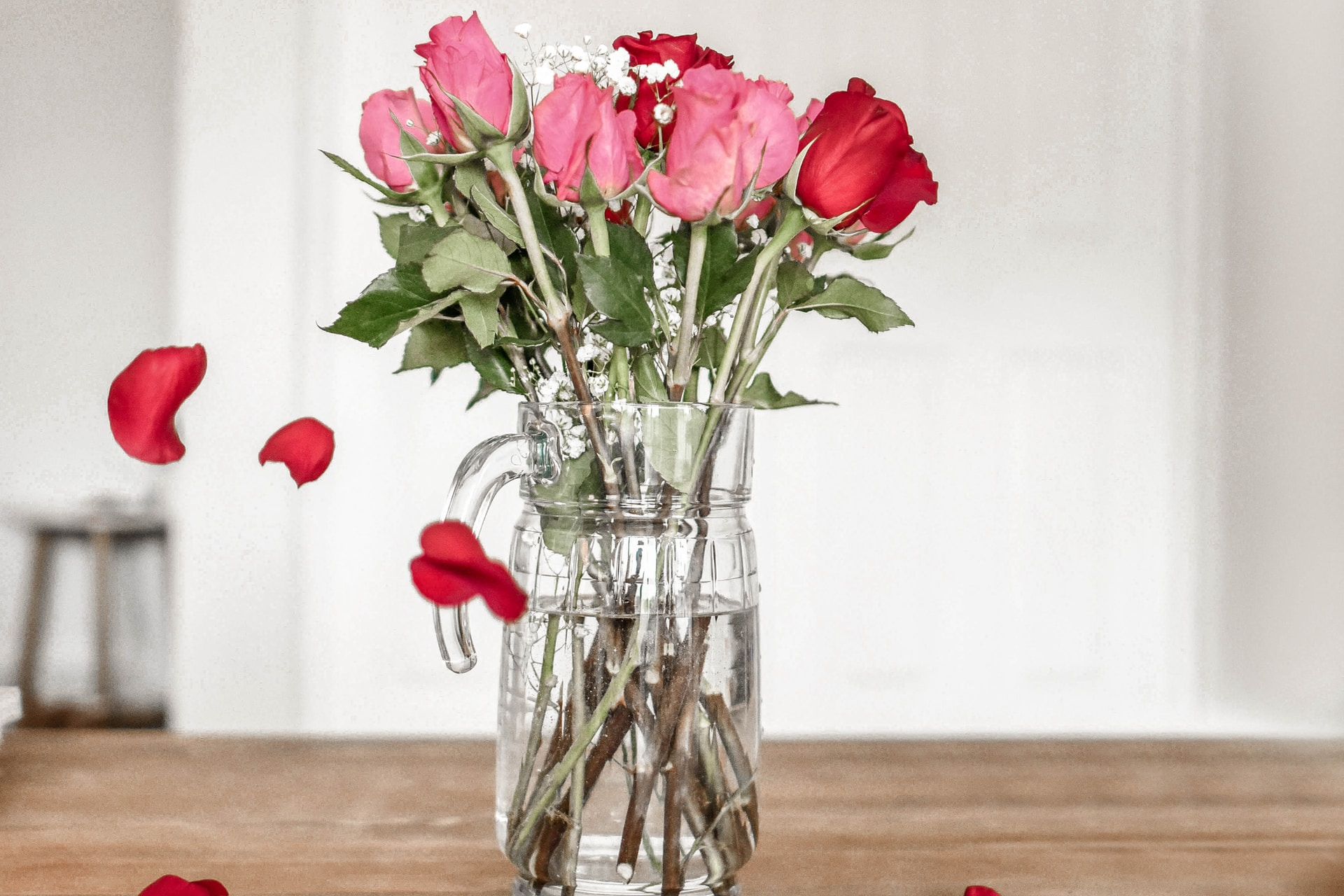 pink and red roses on clear glass vase