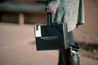 woman holding black paper tote bag