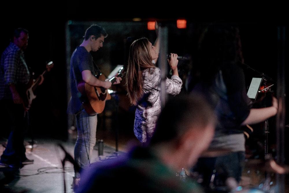 woman holding microphone singing beside man playing guitar